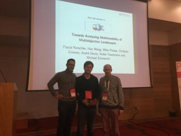 Manuel López-Ibáñez (left) presenting the Best Paper Award to Pascal Kerschke (middle) and Christian Grimme (right).