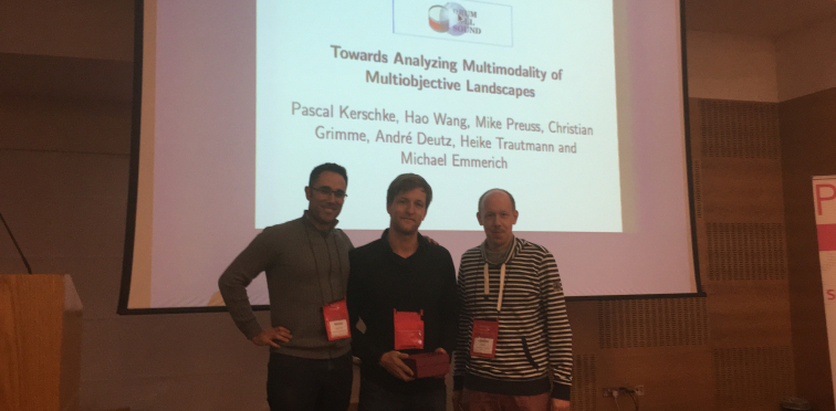 Manuel López-Ibáñez (left) presenting the Best Paper Award to Pascal Kerschke (middle) and Christian Grimme (right).